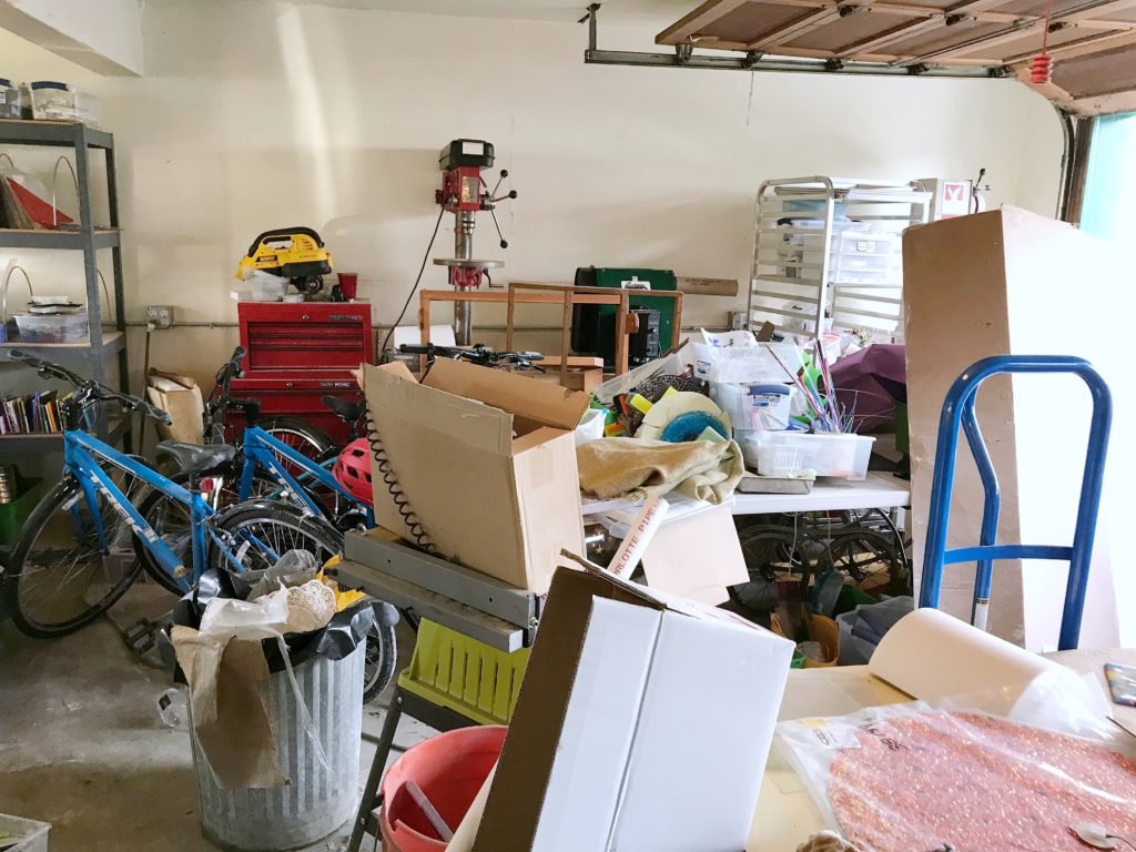 Garage strewn with boxes, glass equipment, and trash
