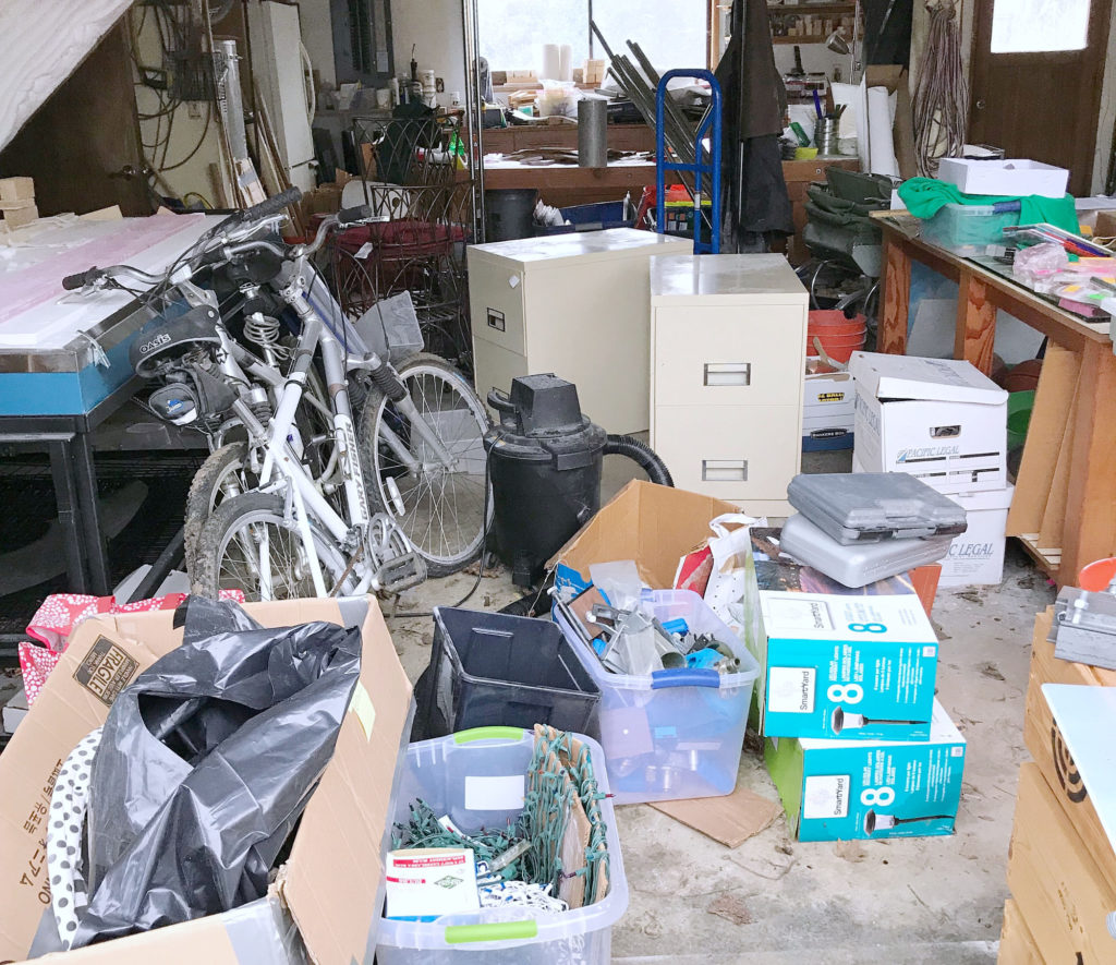 Garage cluttered with boxes, bikes, and filing cabinets