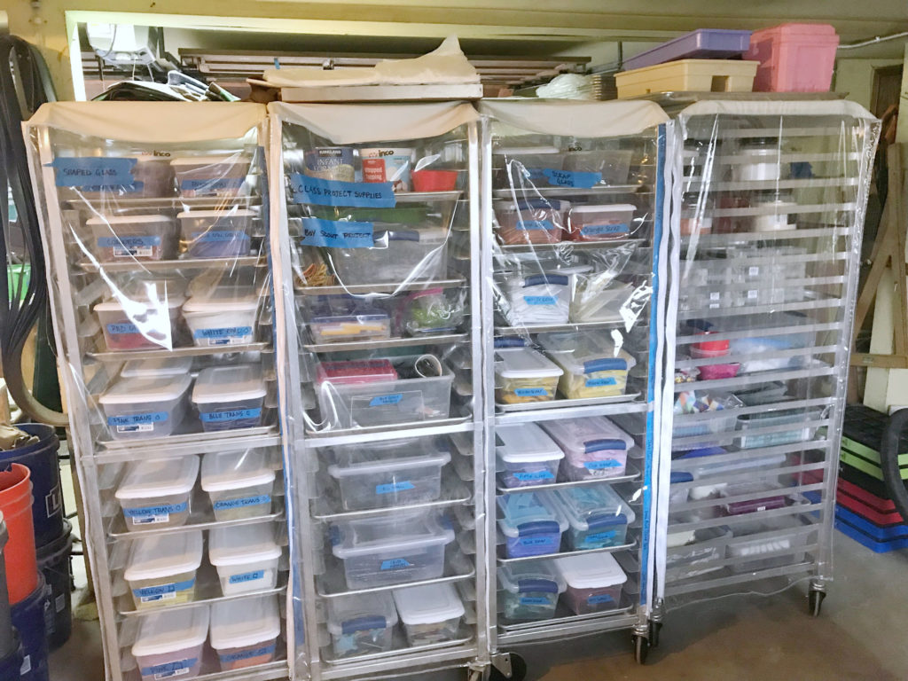Rolling storage racks with bins of glass materials