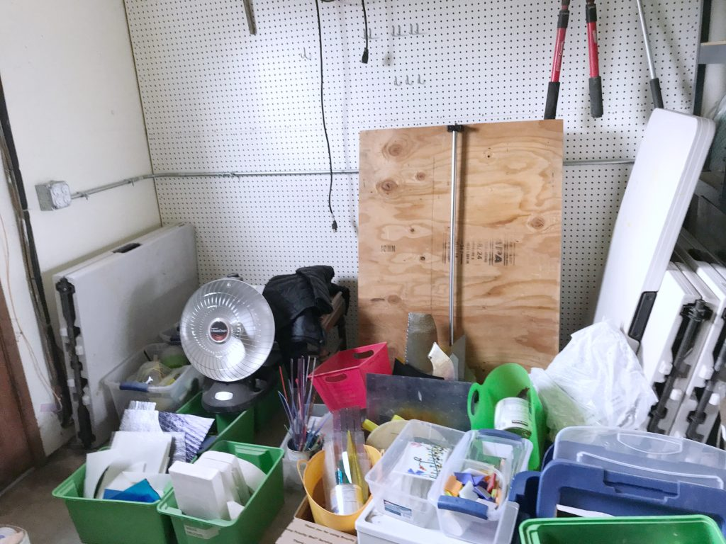 Corner of garage with bins and tables