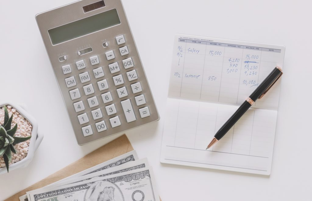 Calculator, check book, and cash to add up costs