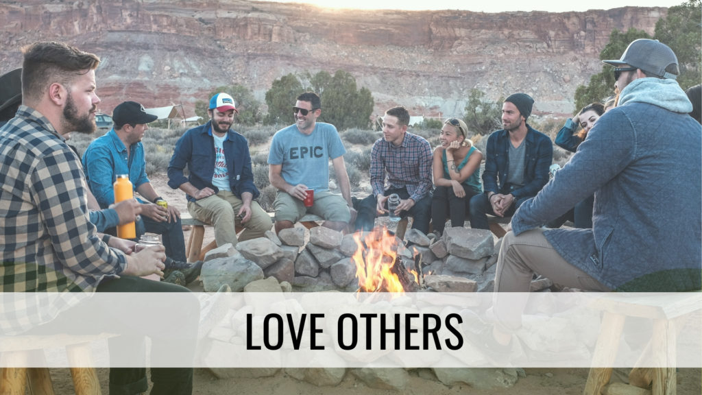 People gathered around campfire - love others