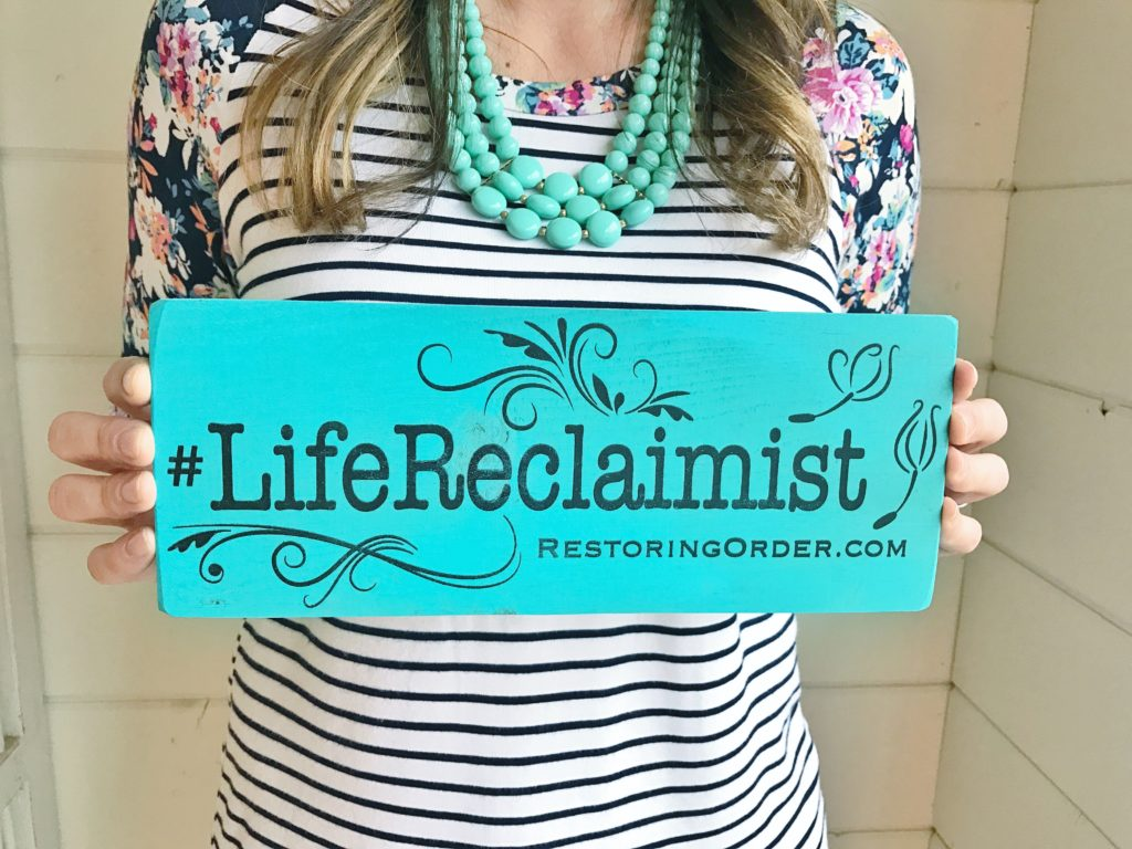 Woman holding life reclaimist sign