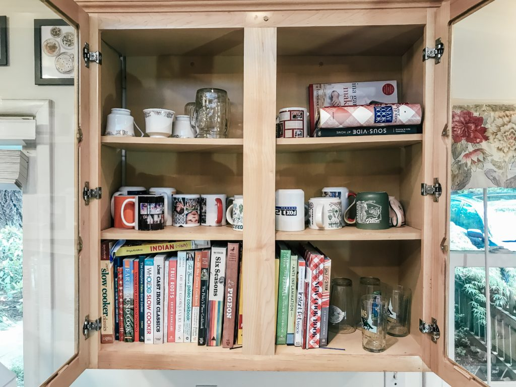 Cabinet with glass doors with mugs and cookbooks