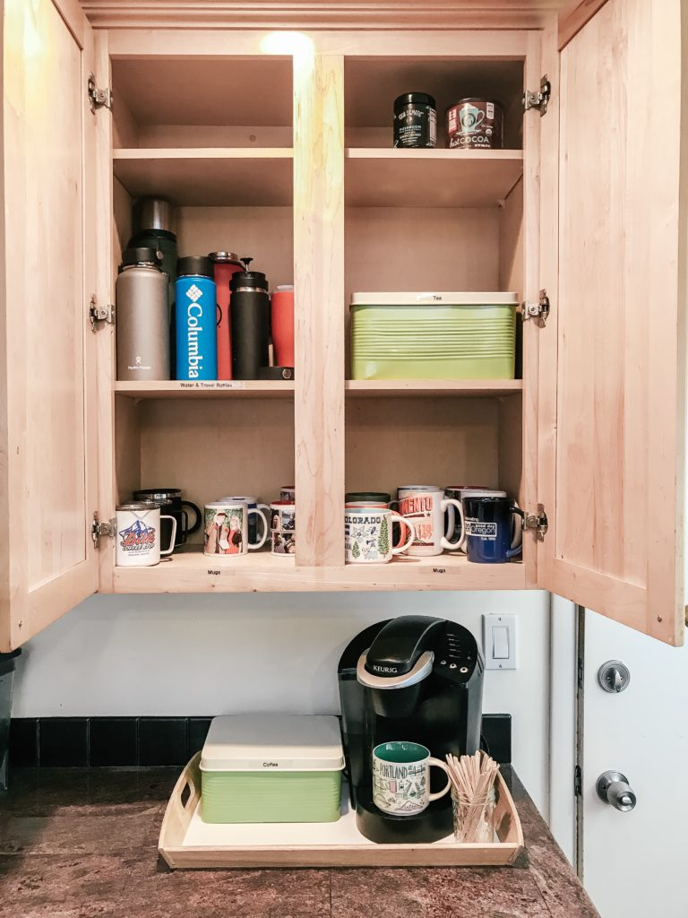 Organized cabinet with water bottles and mugs