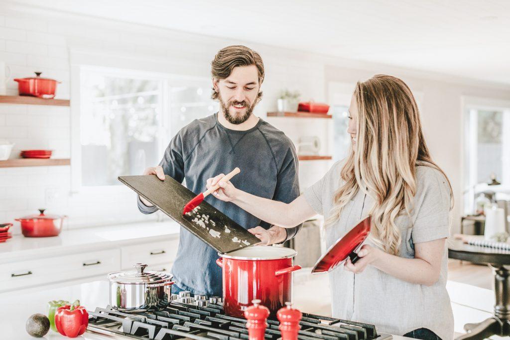 Man and woman cooking dinner together in kitchen